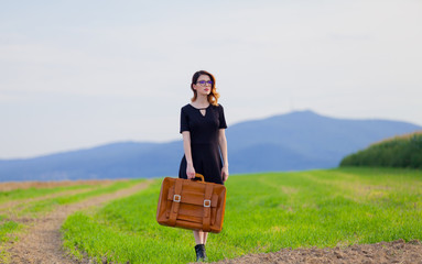 woman at countryside with suitcase