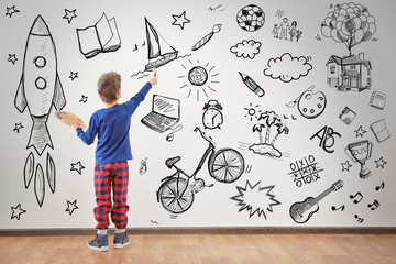 Cute little boy painting on wall in empty room