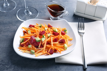 Plate with delicious carrot salad on table