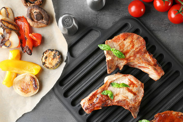 Barbecue grate with tasty grilled steaks on grey table
