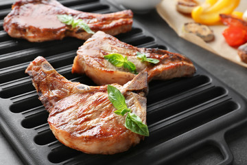 Wall Mural - Barbecue grate with tasty grilled steaks on grey table, close up
