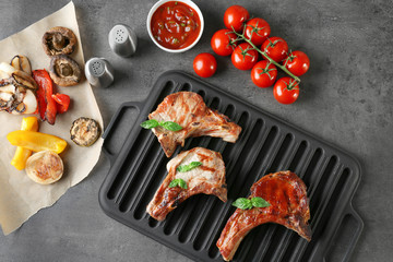 Wall Mural - Barbecue grate with tasty grilled steaks on grey table