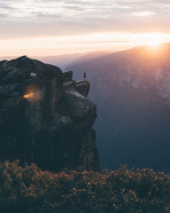 Man standing on cliff of the mountain during sunset