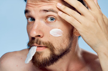 Man with a beard on a blue background, portrait, cosmetic cream, cotton pads