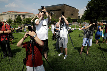 Photographers make picture of the solar eclipse as it passes behind the Washington Monument in Washington