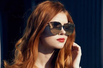 Beautiful woman in sunglasses with red hair, portrait