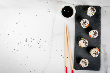 Trend hybrid food. Japanese Asian cuisine. Mini sushi-burgers, sandwiches with salmon, hayashi wakame, daikon, ginger, red caviar. White marble table, with chopsticks, soy sauce. Top view copy space