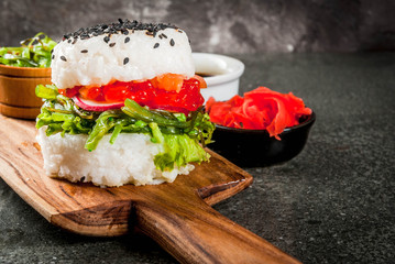 Trend hybrid food. Japanese Asian cuisine. Sushi-burger, sandwich with salmon, hayashi wakame, daikon, ginger, red caviar. Black stone table, with soy sauce. Copy space