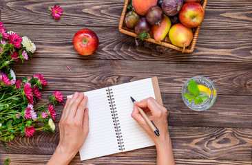 Female hands make notes in notebook on the wooden table with basket of fruits, glass of water and Chrysanthemums flowers. Time for planning. Healthy lifestyle concept. Selective focus. Copy space