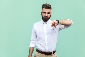 Portrait of unsatisfied bearded man with thumbs down and white shirt against light green background. Studio shot.