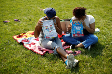 Women use viewers made from cereal boxes to watch a partial solar eclipse in Ottawa
