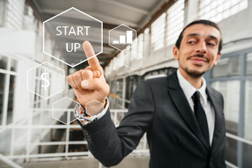 "Businessman pointing with his finger at the abstract business chart with the word ""start up."" The concept of launch and innovation."