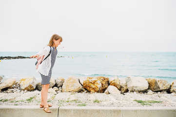 Little girl enjoying summer vacation by the sea, wearing stripe nautical dress and backpack. Image taken in Saintes-Maries-de-la-Mer, capital of Camargue, south of France