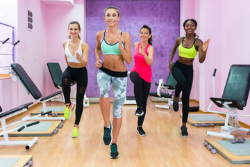 Beautiful women wearing cool sports outfits while running on the spot during HIIT workout class with an experienced female fitness instructor indoors