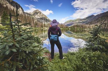 a young woman hiking next to a mountain lake