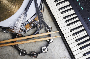 a group of musical instruments including a keyboard, drum, and tambourine.