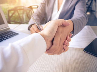 Two of businessman and businesswoman shaking hands in the meeting for success and agreement to express teamwork/togetherness and cooperation concept