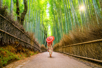 Woman in traditional Yukata with red umbrella at bamboo forest of Arashiyama