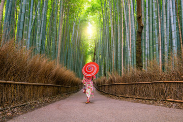 Woman in traditional Yukata with red umbrella at bamboo forest of Arashiyama