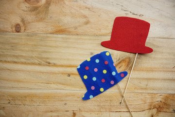 Top or flat lay view of Photo booth props a red hat and a blue polkadot hat on a wooden background flat lay. Birthday parties and weddings.