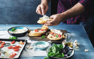 Man is preparing bruschetta with baked tomato, cheese and garlic