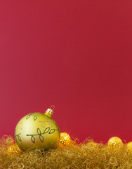 Beautiful hand painted green christmas ball on gold glitter with led lights and red background.