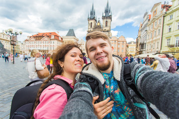 Happy young couple in love takes selfie portrait in Prague, Czech Republic. Pretty tourists make funny photos for travel blog in Europe.