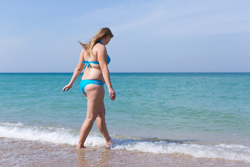 Overweight woman in blue bikini enters the sea water
