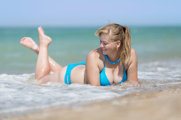 Overweight woman in bikini lying on front in sea foam