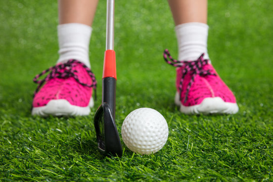 Closeup of a child golfer with putter and ball