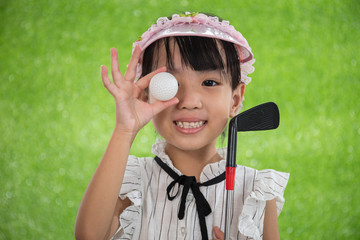 Asian Chinese little girl holding a golf ball