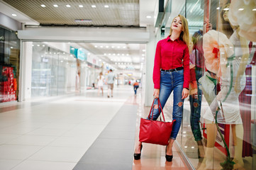 Portrait of a beautiful woman wearing red blouse, casual jeans and black high heels poses with red leather handbag in huge shopping mall.