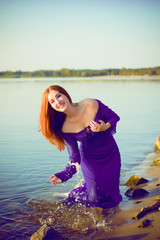 Gorgeous hot young red haired lady at evening sunlight around forest, rocks and water. Woman wearing in purple long dress. Portrait in vintage style.Sweet woman rest on the sea.Nymph on a nature