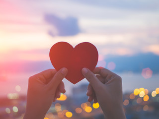 Soft focus hand holding beautiful heart during sunset background. Happy, Love, Valentine's day idea, sign, symbol, concept.