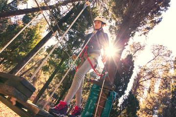 Happy school girl enjoying activity in a climbing adventure park on a summer day