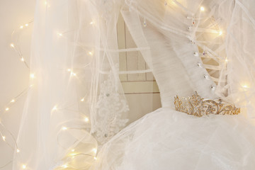 Beautiful white wedding dress and veil on chair with gold garland lights