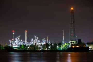 Oil refinery plant near river at twilight dusk