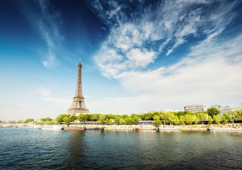 The Eiffel Tower in Paris, France, on a sunny day with the river Seine and dramatic clouds.  Colourful travel background. Popular travel destination