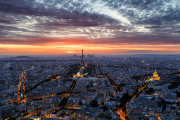 Scenic sunset sky over Paris, France. Aerial panorama view with the Eiffel Tower and the Invalides in the background. Colourful nighttime skyline. Travel background.
