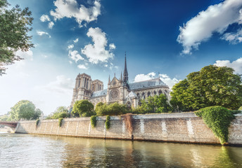 Notre Dame Cathedral in Paris, France, on a sunny day with the river Seine and dramatic clouds.  Scenic skyline.