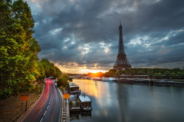 Scenic view over the Eiffel Tower from a bridge at sunrise. Paris, France. Beautiful travel background with rising sun and dramatic clouds.