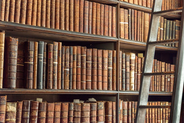 Old vintage books on wooden bookshelf and ladder in a library