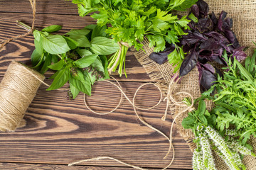 Fresh organic green herbs wooden floor with copy space. Green and violet plants background. Healthy eating background. Vegetarian food, organic food.