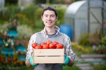 Happy farmer guy with tomato