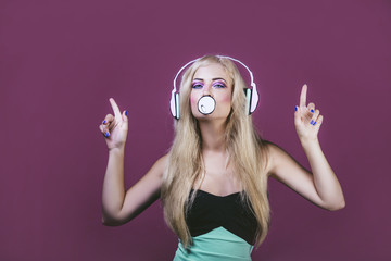 Model woman young and beautiful in the style of pop art on a pink background painted with headphones and bubble gum