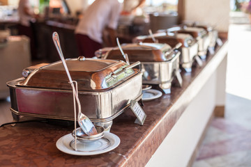 Buffet table. Steam pans arranged in row on the bar.