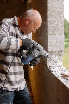 Ouvrier maçon avec perceuse à percussion
