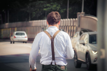 businessman walking on busy city, back view of elegant male in the traffic background