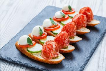 Caprese sandwiches with tomato, mozzarella cheese, basil, salami on ciabatta bread on stone slate background close up. Delicious appetizer snacks, bruschetta, crostini, antipasti. Top view