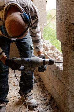 Ouvrier maçon avec perforateur et casque antibruit